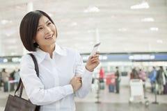 Mujer joven que celebra un billete de avión Imagen de archivo