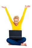 Mujer joven que celebra éxito en la computadora portátil Fotos de archivo