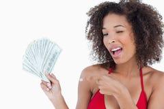 Mujer joven que centella un ojo mientras que sostiene una fan de notas Imágenes de archivo libres de regalías