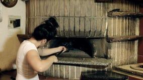 Mujer joven que cepilla su horno metrajes