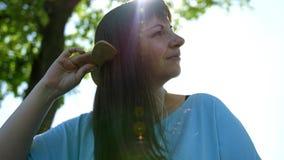 Mujer joven que cepilla su pelo y sonrisa fotos de archivo