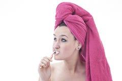 Mujer joven que cepilla sus dientes Foto de archivo