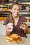 Mujer joven que charla el teléfono móvil con una torta en café Imagen de archivo