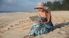 Mujer joven que charla en el ordenador en la playa almacen de metraje de vídeo