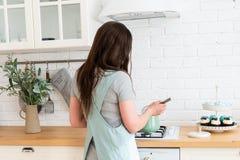 Mujer joven que cocina en la cocina Alimento sano Forma de vida sana El cocinar en el pa?s Preparaci?n del alimento confitero hom fotos de archivo libres de regalías