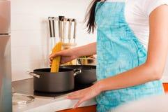 Mujer joven que cocina en la cocina Fotografía de archivo