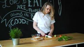 Mujer joven que cocina en la cocina Comida sana - ensalada vegetal Dieta Concepto de dieta Forma de vida sana El cocinar en almacen de video