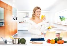 Mujer joven que cocina en una cocina moderna Imagen de archivo libre de regalías