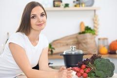 Mujer joven que cocina en una cocina Sopa de la prueba del ama de casa por la cuchara de madera fotos de archivo