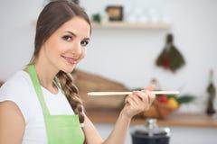 Mujer joven que cocina en una cocina Sopa de la prueba del ama de casa por la cuchara de madera foto de archivo