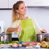 Mujer joven que cocina la carne en casa Imagen de archivo libre de regalías