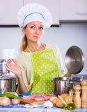 Mujer joven que cocina la carne en casa Imagen de archivo