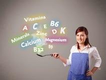 Mujer joven que cocina las vitaminas y los minerales Fotografía de archivo