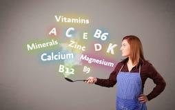Mujer joven que cocina las vitaminas y los minerales Foto de archivo