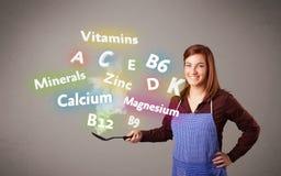 Mujer joven que cocina las vitaminas y los minerales Imagen de archivo libre de regalías