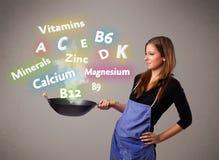 Mujer joven que cocina las vitaminas y los minerales Imagenes de archivo