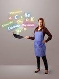 Mujer joven que cocina las vitaminas y los minerales Imagen de archivo