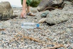 Mujer joven que coge la basura plástica de la botella, limpiando en la tira costera fotografía de archivo libre de regalías