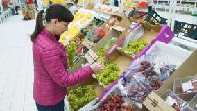 Mujer joven que coge las uvas para la compra almacen de video