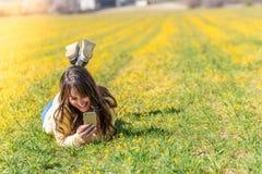 Mujer joven que coloca usando el tel?fono m?vil fotos de archivo libres de regalías