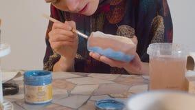 Mujer joven que colorea un cuenco almacen de metraje de vídeo