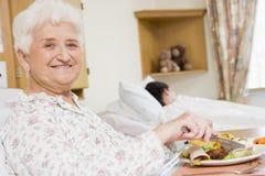 Mujer joven que come el alimento del hospital foto de archivo libre de regalías