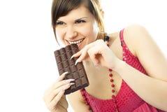 Mujer joven que come el chocolate Foto de archivo