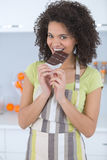 Mujer joven que come el chocolate en fondo ligero Imagen de archivo libre de regalías