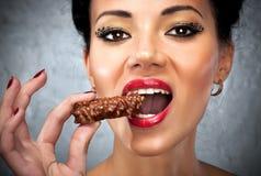 Mujer joven que come el dulce Foto de archivo libre de regalías