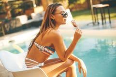 Mujer joven que come el helado cerca de la piscina fotografía de archivo