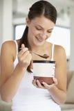 Mujer joven que come el helado del chocolate Foto de archivo libre de regalías
