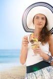 Mujer joven que come el helado en la playa del verano Imagen de archivo libre de regalías