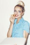 Mujer joven que come el pedazo de pizza Imágenes de archivo libres de regalías