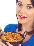Mujer joven que come el pollo Tikka Biryani Fotos de archivo libres de regalías