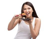 Mujer joven que come el sushi con palillos Imagen de archivo