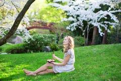 Mujer joven que come el sushi en parque japonés Foto de archivo libre de regalías