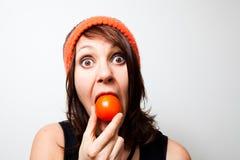 Mujer joven que come el tomate fotografía de archivo