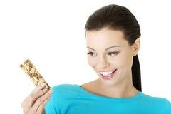 Mujer joven que come la barra de caramelo del cereal Imagen de archivo libre de regalías