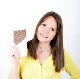 Mujer joven que come la barra de chocolate contra el fondo blanco Imágenes de archivo libres de regalías