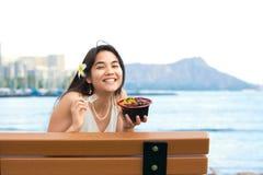 Mujer joven que come la carne de vaca hawaiana del bqq en banco en Hawaii Imágenes de archivo libres de regalías
