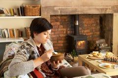 Mujer joven que come la cena por el fuego Fotografía de archivo libre de regalías