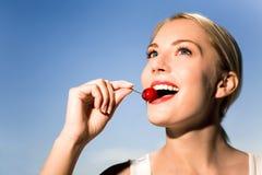 Mujer joven que come la cereza Fotos de archivo