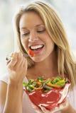 Mujer joven que come la ensalada Foto de archivo libre de regalías