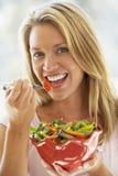 Mujer joven que come la ensalada fresca imagen de archivo libre de regalías