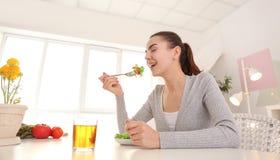 Mujer joven que come la ensalada fresca en casa Concepto sano del alimento fotografía de archivo libre de regalías