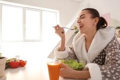 Mujer joven que come la ensalada fresca en casa Concepto sano del alimento imagen de archivo libre de regalías