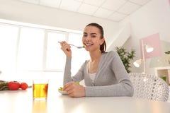 Mujer joven que come la ensalada fresca en casa Concepto sano del alimento fotografía de archivo