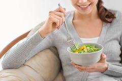Mujer joven que come la ensalada fresca en casa Concepto sano del alimento imagen de archivo