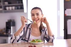 Mujer joven que come la ensalada fresca en casa Concepto sano del alimento imagenes de archivo