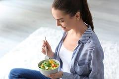 Mujer joven que come la ensalada fresca en casa Concepto sano del alimento foto de archivo libre de regalías